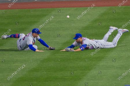 New York Mets center fielder Brandon Nimmo, left, and right fielder Michael Conforto stumble over a triple hit by Philadelphia Phillies' Andrew McCutchen during the eighth inning of a baseball game, in Philadelphia