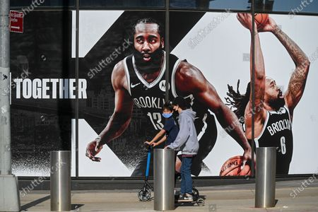 People walk past a mural of American basketball player James Harden on the Barclays Center in New York.