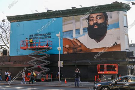 Artists paint a mural of American basketball player James Harden on a building across from the Barclays Center in New York.