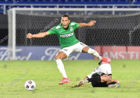 Michael Chacon of Colombia's Atletico Nacional, top, fights for the ball with Carlos Ferreira of Paraguay's Libertad during a Copa Libertadores soccer match at Defensores del Chaco stadium in Asuncion, Paraguay