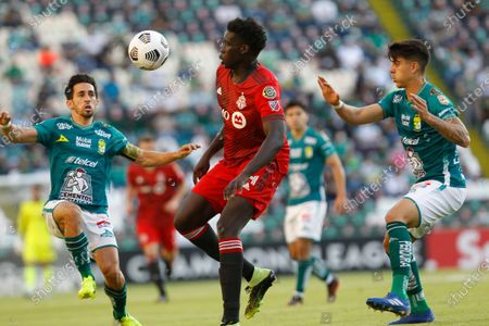 Noble Okello of Canada's Toronto FC, center, fights for the ball with Fernando Navarro, left, and Santiago Colombatto of Mexico's Leon during their Concacaf Champions League soccer match in Leon, Mexico, in Leon