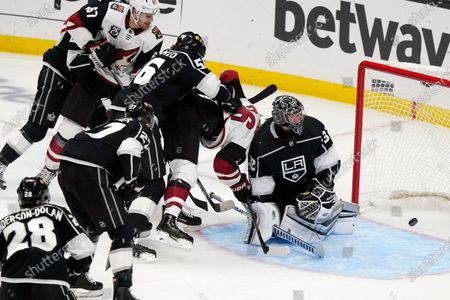 Los Angeles Kings goaltender Jonathan Quick, right, gives up a goal on a shot from Arizona Coyotes left wing Lawson Crouse, top left, during the first period of an NHL hockey game, in Los Angeles