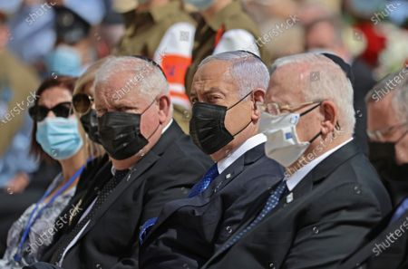 Israeli President Reuven Rivlin (R) alongside Prime Minister Benjamin Netanyahu (C) attend a wreath-laying ceremony marking the Holocaust Remembrance Day at Warsaw Ghetto Square in Jerusalem's Yad Vashem memorial on 08 April 2021.