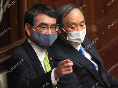 Japanese Prime Minister Yoshihide Suga (R) chats with Administrative Reform minister Taro Kono (L) at lower House's plenary session at the National Diet in Tokyo on Thursday, April 8, 2021.