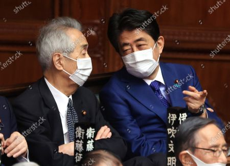 Former Japanese Prime Minister Shinzo Abe (R) chats with former parliament speaker Bunmei Ibuki (L) at lower House's plenary session at the National Diet in Tokyo on Thursday, April 8, 2021.