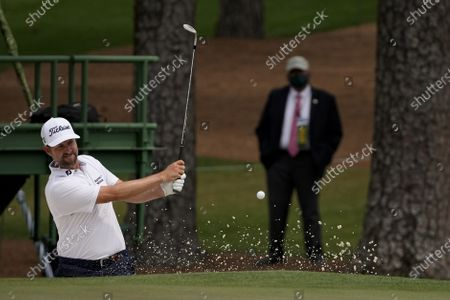 Webb Simpson hits out of a bunker on the 15th hole during the first round of the Masters golf tournament, in Augusta, Ga