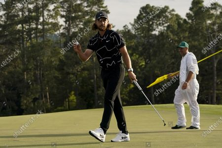 Tommy Fleetwood, of England, holds up his ball after his putt on the 18th hole during the first round of the Masters golf tournament, in Augusta, Ga