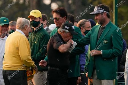 Gary Player kisses Bubba Watson's hand while Phil Mickelson greets Jack Nicklaus before the ceremonial first tee shot during the first round of the Masters golf tournament, in Augusta, Ga