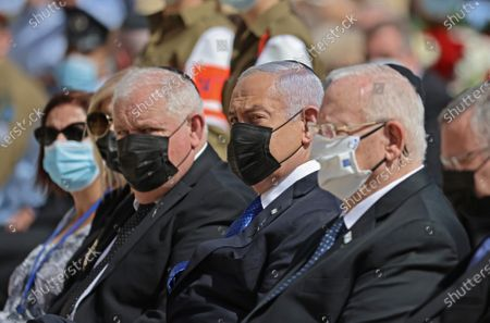 Israeli President Reuven Rivlin (R) alongside Prime Minister Benjamin Netanyahu (C) attend a wreath-laying ceremony marking the Holocaust Remembrance Day at Warsaw Ghetto Square in Jerusalem's Yad Vashem memorial on Thursday, April 8, 2021.