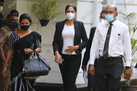 Stock Image of Mrs. World Caroline Jurie (C) flanked by her lawyers walk out of the Cinnamon Gardens Police station after being enlarged on police bail in Colombo, Sri Lanka, 08 April 2021. Reigning Mrs. World Caroline Jurie and model and catwalk trainer Chula Padmendra were arrested by the Cinnamon Gardens Police earlier today 08 April on three separate counts, following a complaint filed by Pushpika De Silva who won the Mrs. Sri Lanka 2020 title during a pageant at the Nelum Pokuna Theatre in Colombo.  Jurie who was among the panel of judges declared that she takes the first step to disqualify  De Silva as she is a divorcee, removed the crown and declared the runner-up as the winner. De Silva claimed that she is not divorced but in fact is only separated and thus is qualified and lodged a complaint that she was injured while the crown was being removed hastily. The next day, the organisers of the pageant took steps to restore the crown on Ms. Pushpika De Silva and requested Jurie to apologies for the ugly incident.