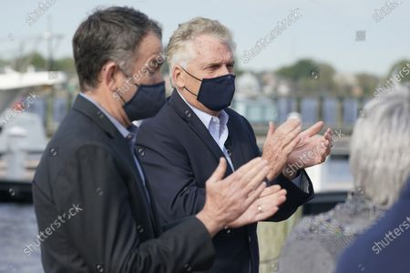 Virginia Gov. Ralph Northam, left, applauds speakers with former Gov. and Democratic gubernatorial candidate, Terry McAuliffe, right, during a news conference at Waterside in Norfolk, Va., . Northam endorsed McAuliffe for governor