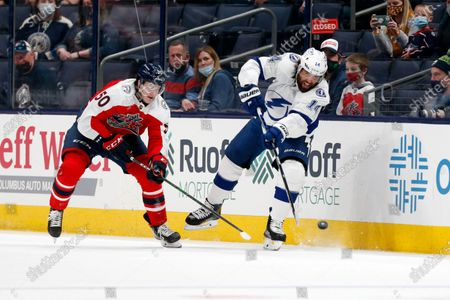 Tampa Bay Lightning forward Pat Maroon, right, passes in front of Columbus Blue Jackets forward Eric Robinson during an NHL hockey game in Columbus, Ohio, . The Blue Jackets won 4-2
