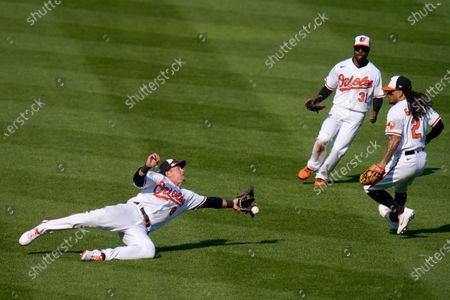 Baltimore Orioles left fielder Ryan Mountcastle, left, attempts a diving catch on a ball hit by Boston Red Sox's Christian Vazquez during the sixth inning of a baseball game, on Opening Day in Baltimore. Orioles Cedric Mullins (31) and Freddy Galvis (2) look on