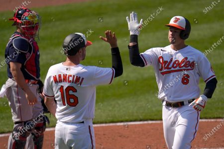 Baltimore Orioles' Ryan Mountcastle, right, is greeted by Trey Mancini, center, after Mountcastle scored them both on a two-run home run off Boston Red Sox starting pitcher Eduardo Rodriguez during the first inning of a baseball game, on Opening Day in Baltimore. Red Sox's catcher Christian Vazquez, left, looks on