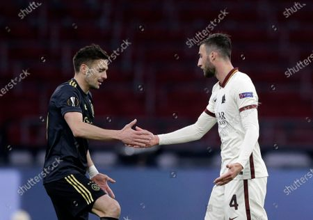 Ajax's Dusan Tadic, left, shakes hands with Roma's Bryan Cristante during the Europa League first leg quarterfinal soccer match between Ajax and Roma at the Johan Cruyff ArenA in Amsterdam, Netherlands