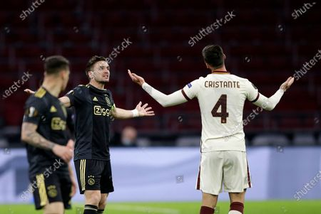 Ajax's Dusan Tadic, center, argues with Roma's Bryan Cristante during the Europa League first leg quarterfinal soccer match between Ajax and Roma at the Johan Cruyff ArenA in Amsterdam, Netherlands