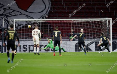 Roma's goalkeeper Pau Lopez, center, makes a save penalty in front of Ajax's Dusan Tadic, right, during the Europa League first leg quarterfinal soccer match between Ajax and Roma at the Johan Cruyff ArenA in Amsterdam, Netherlands