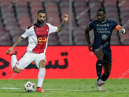Al-Ahli's player Motaz Hawsawi (R) in action against Al-Raed's Ronnie Fernandez (L) during the Saudi Professional League soccer match between Al-Ahli and Al-Raed at King Abdulaziz Stadium, in Mecca, Saudi Arabia, 08 April 2021.