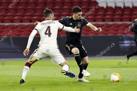 Bryan Cristante (L) of AS Roma and Dusan Tadic of Ajax in action during the UEFA Europa League quarterfinal, 1st leg soccer match between Ajax Amsterdam and AS Roma at the Johan Cruijff Arena in Amsterdam, The Netherlands, 08 April 2021.