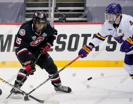 St. Cloud State's Micah Miller (15) chips the puck past Minnesota State's Andy Carroll (4) during the second period of an NCAA hockey semifinal game at the Frozen Four in Pittsburgh
