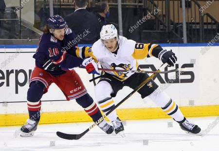 New York Rangers' Artemi Panarin (10) holds back Pittsburgh Penguins' John Marino (6) during the first period of an NHL hockey game, in New York