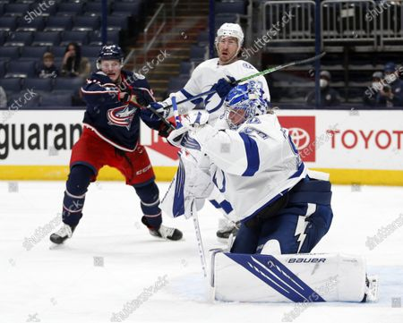 Tampa Bay Lightning goalie Andrei Vasilevskiy, right, stops a shot in front of Columbus Blue Jackets forward Eric Robinson, left, and Lightning defenseman Ryan McDonagh during the second period of an NHL hockey game in Columbus, Ohio