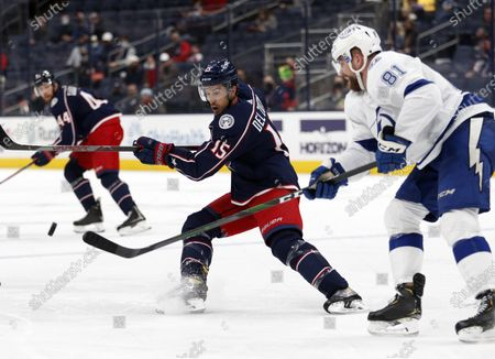 Columbus Blue Jackets defenseman Michael Del Zotto, left, reaches for the puck in front of Tampa Bay Lightning defenseman Erik Cernak during the second period of an NHL hockey game in Columbus, Ohio