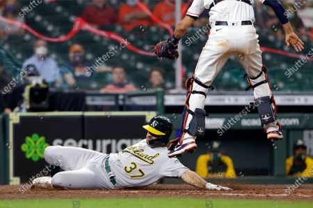 Oakland Athletics' Aramis Garcia (37) slides safely into home as Houston Astros catcher Jason Castro jumps for the throw during the ninth inning of a baseball game, in Houston