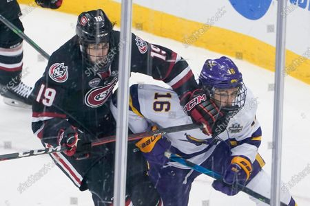 St. Cloud State's Sam Hentges (19) checks Minnesota State's Reggie Lutz (16) during the third period of an NCAA men's Frozen Four hockey semifinal in Pittsburgh, . St. Cloud State won 5-4