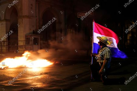 Man carries a national flag during a protest in front of the Congress building, asking for the resignation of President Mario Abdo Benitez over his handling of the coronavirus pandemic and the state of the public health system, in Asuncion, Paraguay