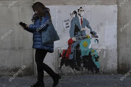 "Woman walks past a poster depicting a scene from the famed movie "" Roman Holiday"" with Gregory Peck and Audrey Hepburn wearing surgical masks as riding a Lambretta scooter in Rome, . Italy has seen a stabilizing of the new variant-fueled infections over the past three weeks, though its daily death count remains stubbornly high, averaging between 300-500 COVID-19 victims per day, and its ICU capacity for virus patients is well over the threshold set by the government"