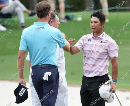 Hideki Matsuyama fist bumps with Harris English as they finish the eighteenth hole during the second round of the 2021 Masters Tournament at Augusta National Golf Club