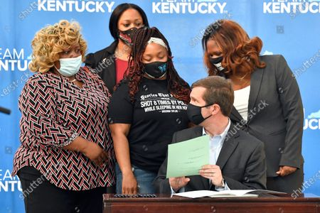 Kentucky Governor Andy Beshear talks with Tamika Palmer, the mother of Breonna Taylor, back row center, following the signing of a partial ban on no-knock warrants at the Center for African American Heritage Louisville, Ky., . The bill signing comes after months of demonstrations set off by the fatal shooting of Taylor in her home during a botched police raid