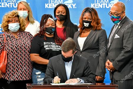 Stock Photo of Kentucky Gov. Andy Beshear signs a bill creating a partial ban on no-knock warrants, at the Center for African American Heritage Louisville, Ky. At the signing is Tamika Palmer, the mother of Breonna Taylor, behind Governor left. The bill signing comes after months of demonstrations set off by the fatal shooting of Taylor in her home during a botched police raid