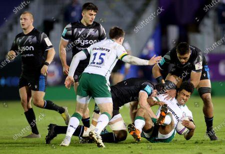 Bath Rugby vs London Irish. Bath's Josh Bayliss and Taulupe Faletau tackle Ben Loader of London Irish