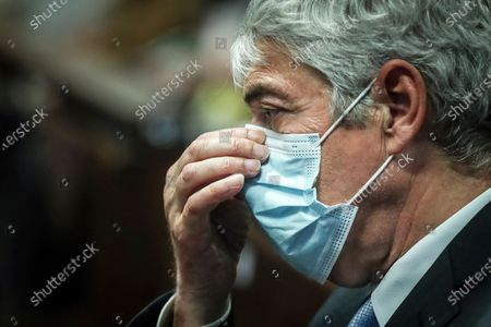 Former Portuguese prime minister Jose Socrates adjusts his face mask while siting in a courtroom in Lisbon, to hear a judge decision whether evidence gathered by public prosecutors is sufficient to put him on trial for alleged corruption, money laundering and tax fraud, . A Lisbon judge on Friday sent Socrates for trial on charges of money-laundering and forgery but said the statute of limitations had expired on more than a dozen allegations of corruption against him