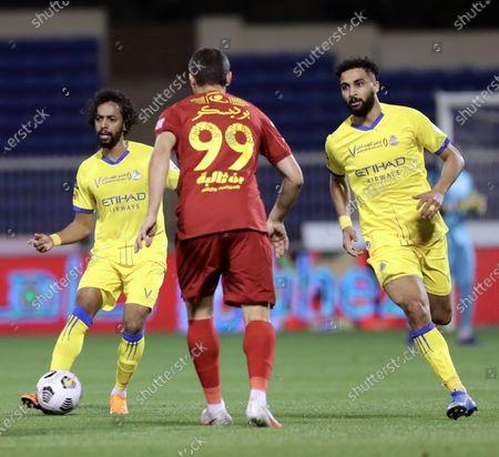 Damac's player Constantin Budescu (C) in action against Al-Nassr's Abdulmajeed Al-Sulaiheem (L) and Abdulrahman Al-Obaid (R) during the Saudi Professional League soccer match between Damac and Al-Nassr at Prince Sultan bin Abdul Aziz Stadium, in Abha, Saudi Arabia, 09 April 2021.