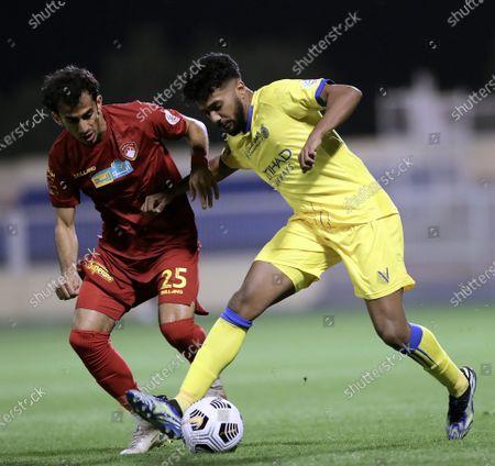 Damac's player Arif Al-Haydar (L) in action against Al-Nassr's Khalid Al-Ghannam (R) during the Saudi Professional League soccer match between Damac and Al-Nassr at Prince Sultan bin Abdul Aziz Stadium, in Abha, Saudi Arabia, 09 April 2021.