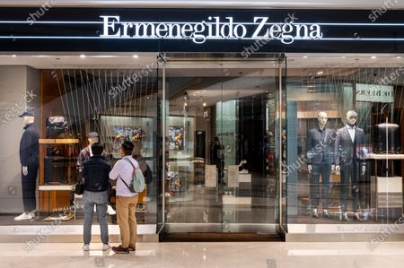 Stock Photo of Shoppers stand in front of the Italian luxury fashion brand Ermenegildo Zegna store seen in Hong Kong.