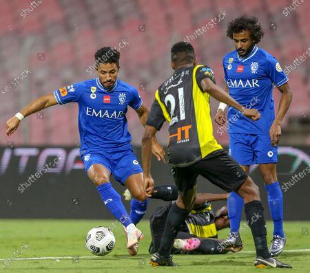 Stock Photo of Al-Ittihad's player Abdulmohsen Fallatah (C) in action against Al-Hilal's Hattan Bahebri (L) during the Saudi Professional League soccer match between Al-Ittihad and Al-Hilal at King Abdulaziz Stadium, in Mecca, Saudi Arabia, 09 April 2021.