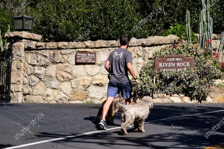 Man walks his dogs past the community gate of the home of Prince Harry The Duke of Sussex and Meghan Markle The Duchess of Sussex after the announcement regarding the death of Britain's Prince Philip, in Montecito, Calif