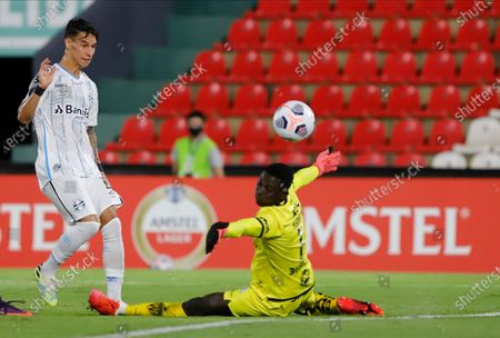 Goalkeeper Wellington Ramirez of Ecuador's Independiente del Valle attempts to block a shot by Ferreira of Brazil's Gremio yet failed to score, during a Copa Libertadores soccer game in Asuncion, Paraguay