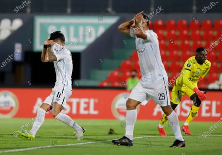 Ferreira of Brazil's Gremio reacts after he fails to score against Ecuador's Independiente del Valle during a Copa Libertadores soccer game in Asuncion, Paraguay, . Also pictured are teammate Diego Souza and Ecuador's goalkeeper Wellington Ramirez