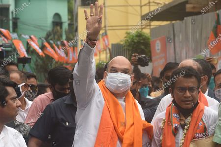Stock Photo of Union Home Minister and Bharatiya Janata Party (BJP) leader Amit Shah and candidate Rudranil Ghosh (R) greeting people during a door-to-door campaign for the Assembly Elections in the state, at Bhowanipore on April 9, 2021 in Kolkata, India.