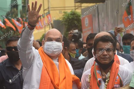 Stock Image of Union Home Minister and Bharatiya Janata Party (BJP) leader Amit Shah and candidate Rudranil Ghosh (R) greeting people during a door-to-door campaign for the Assembly Elections in the state, at Bhowanipore on April 9, 2021 in Kolkata, India.