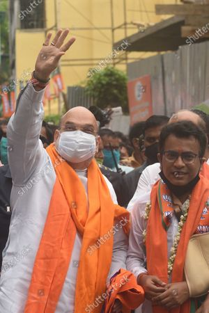 Stock Picture of Union Home Minister and Bharatiya Janata Party (BJP) leader Amit Shah and candidate Rudranil Ghosh (R) greeting people during a door-to-door campaign for the Assembly Elections in the state, at Bhowanipore on April 9, 2021 in Kolkata, India.
