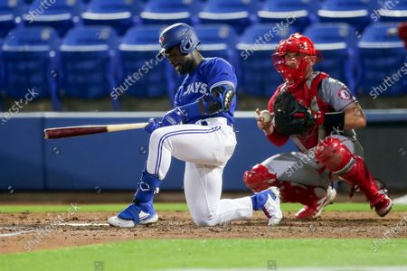 Toronto Blue Jays' Jonathan Davis strikes out in front of Los Angeles Angels catcher Max Stassi during the seventh inning of a baseball game, in Dunedin, Fla