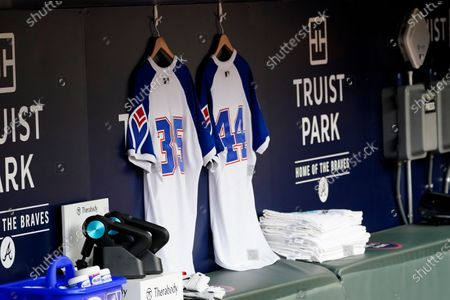 Atlanta Braves jerseys baring the numbers (35) for former Braves players Phil Niekro and (44) for Hank Aaron are hung in the dugout before a baseball game against the Philadelphia Phillies, in Atlanta. Both Aaron and Niekro died in the off season