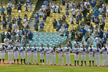 Stock Picture of The Los Angeles Dodgers and their fans hold a moment of silence in memory of former manager Tommy LaSorda before their their home opener against the Washington Nationals at Dodger Stadium in Los Angeles on Friday, April 9, 2021. Playing their first game in front of fans at Dodger Stadium in 18 months, the Dodgers defeated the Nationals 1-0.