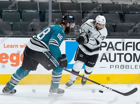 Los Angeles Kings right wing Alex Iafallo (19) takes a shot at goal past San Jose Sharks defenseman Brent Burns (88) during the second period of an NHL hockey game, in San Jose, Calif